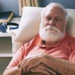 Пожилой мужчина дремлет на кушетке.